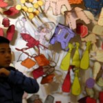 A child in front of drawings of objects.