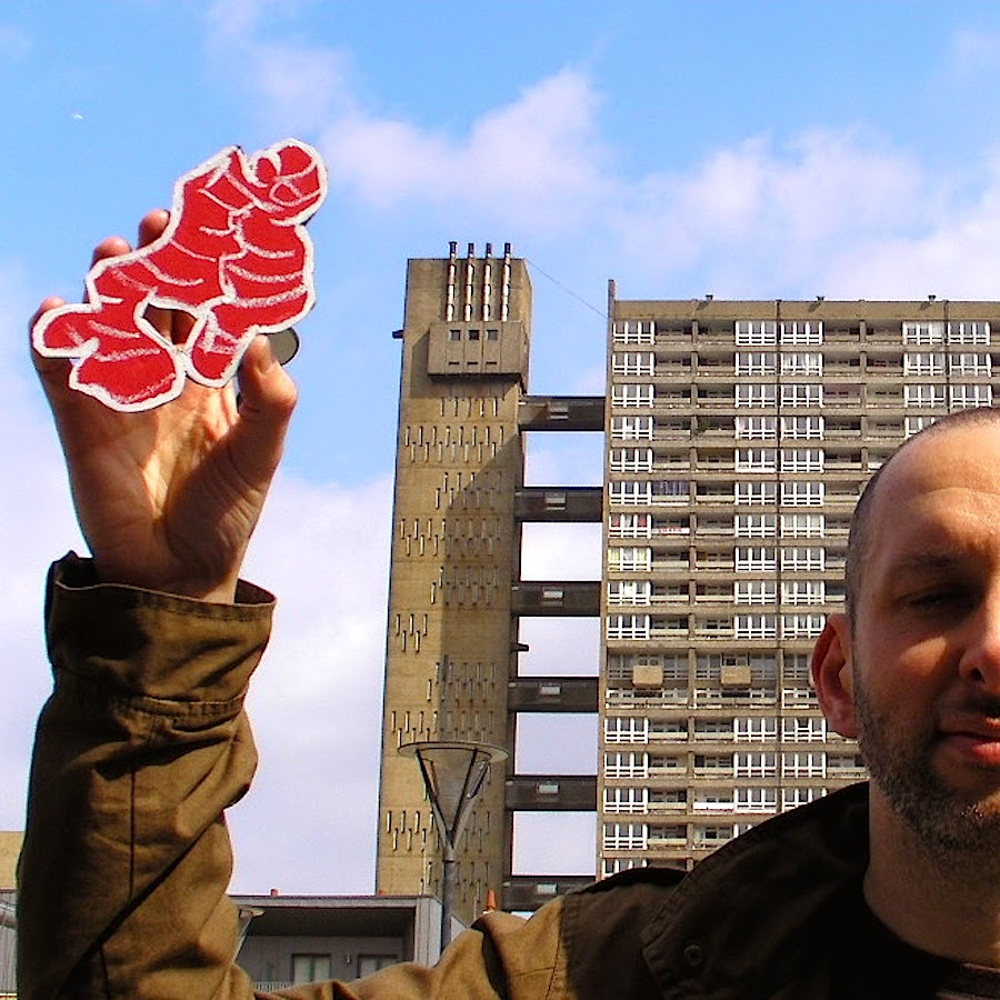 Holding a drawing of Root Ginger, outside Balfron tower, Poplar.
